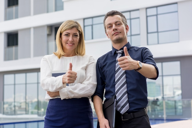 Two smiling male and female business people showing thumbs up outdoors.