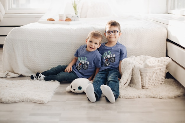 Two smiling male kid posing together at comfortable white bedroom interior. happy brothers hugging having fun at cosiness home sitting on floor near bed