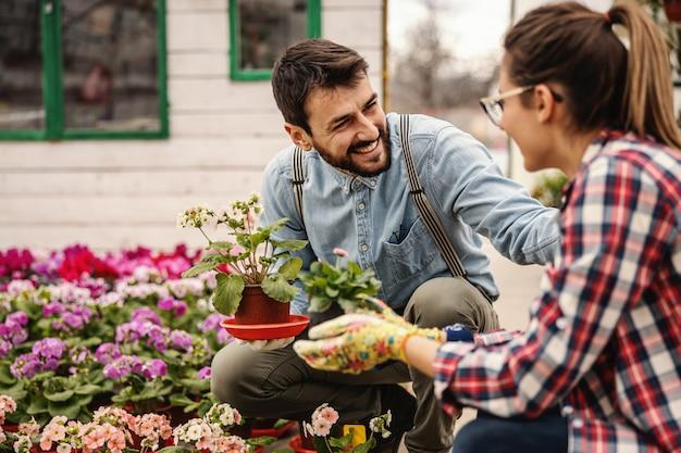 Два улыбающихся работника детского сада сидят на корточках и держат горшки с цветами и болтают.