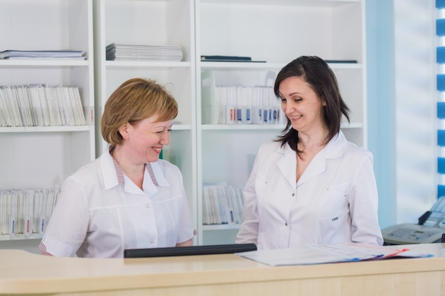 Two smiling nurses working at hospital reception desk