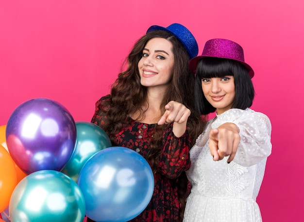 Two smiling and pleased young party girls wearing party hat standing behind balloons both looking and pointing isolated on pink wall