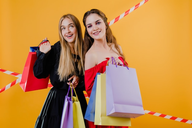 Two smiling pretty girls  with colorful shopping bags isolated over yellow