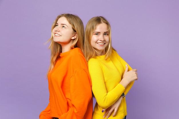 두 웃는 꽤 젊은 금발 쌍둥이 자매 여자 파스텔 바이올렛 블루 벽에 연달아 서 생생한 화려한 옷을 입고. 사람들이 가족 라이프 스타일 개념.