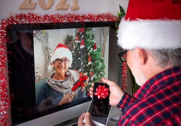 Two smiling senior people with santa hats in video call with computer opening christmas gifts. old active retirees addicted with new technologies. lockdown due to coronavirus covid-19