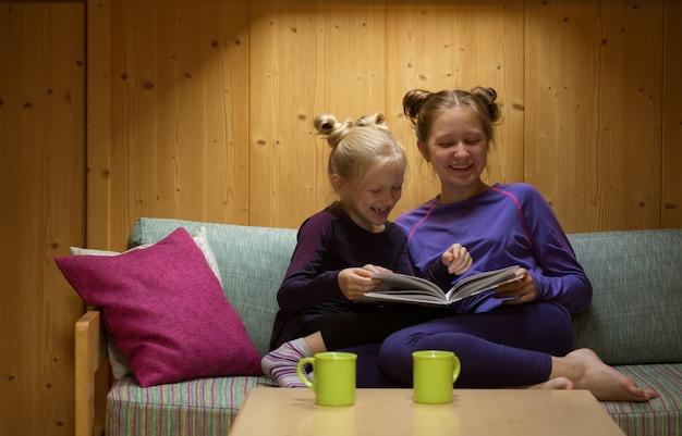2人の笑顔の姉妹の女の子があなたの部屋で本を読みます