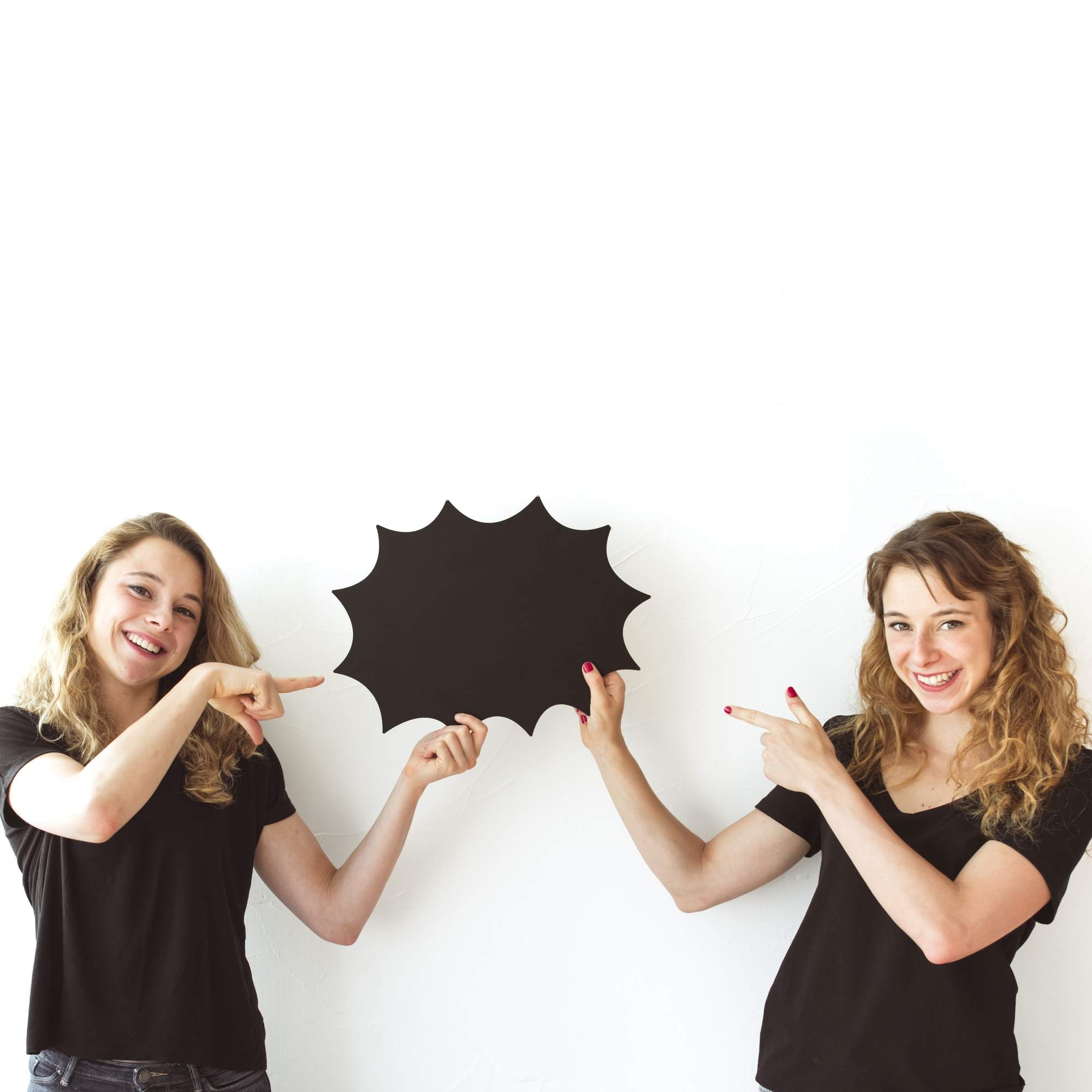 Two smiling sisters holding black speech bubble pointing fingers