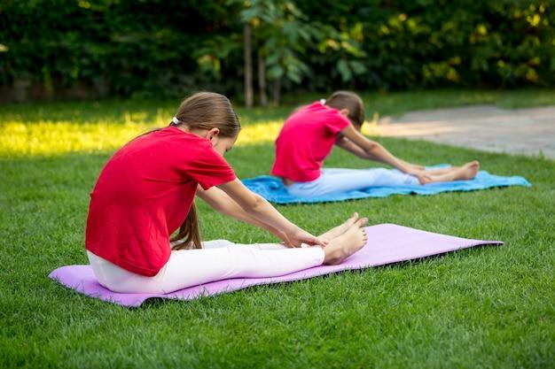 Две улыбающиеся сестры, практикующие йогу на траве на заднем дворе