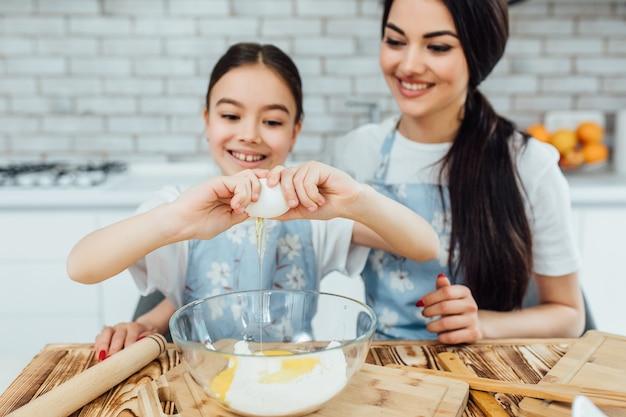 계란을 들고 웃는 두 자매는 부엌에서 요리한다