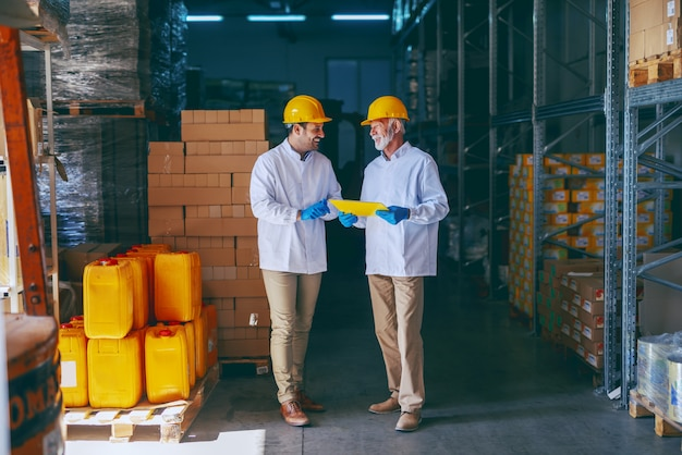 Two smiling warehouse workers in white uniforms and yellow helmets on heads standing and talking about job. older one holding folder with documents in hands.