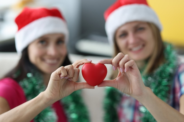 Two smiling woman in santa hats hold heart