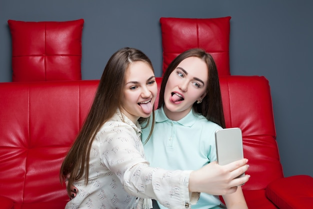 Two smiling woman sitting on red leather couch and makes selfie on phone camera.