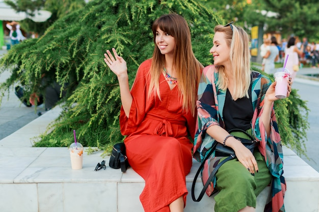 Two smiling woman talking and spending time  together in sunny modern city
