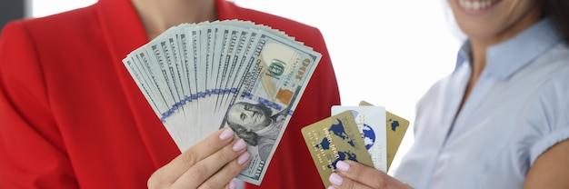 2人の笑顔の女性が100米ドル札とクレジットバンクカードのファンを抱えています。インターネットの概念でフリーランスとお金を稼ぐリモートワーク
