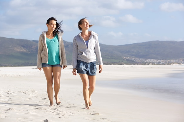 Two smiling women friends walking on beach together