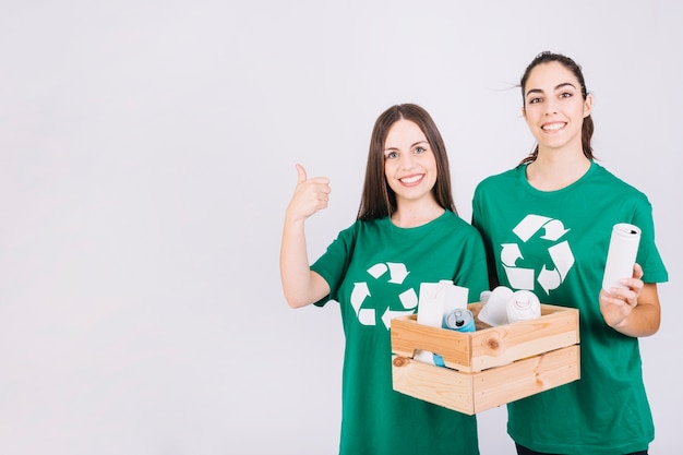 Two smiling women gesturing thumbs up while holding wooden box with recycle items