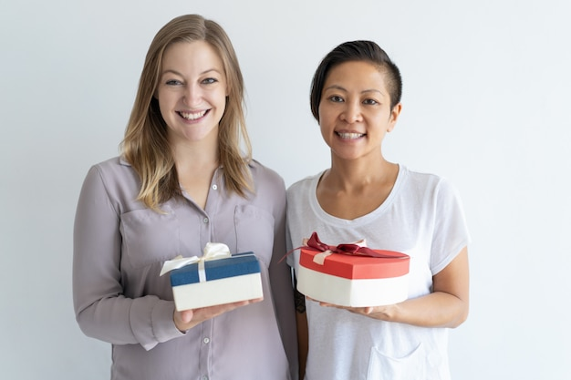 Two smiling women holding gift boxes