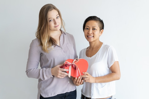 Two smiling women holding red heart shaped gift box