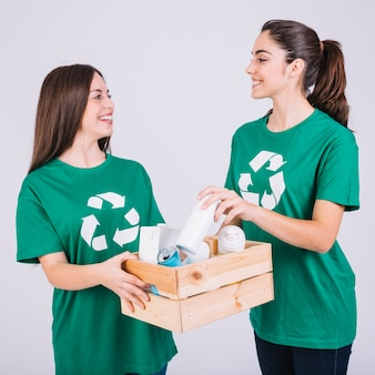 Two smiling women holding wooden box with recycle items