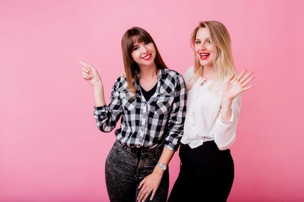 Две улыбающиеся женщины обнимаются и стоят вместе