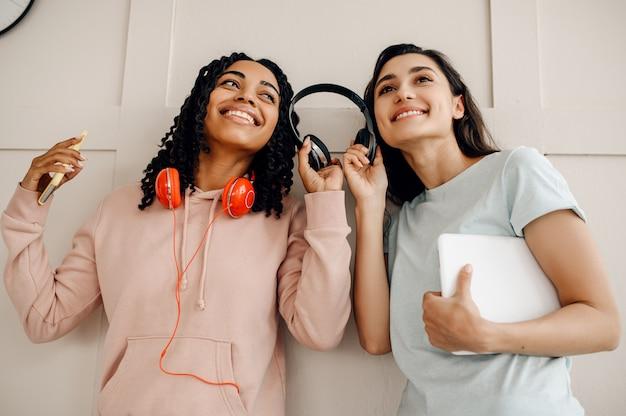 ヘッドフォンで室内で音楽を聴いている 2 人の笑顔の女性。イヤホンをしたかわいいガールフレンドが部屋でリラックスし、音楽愛好家が休んでいる