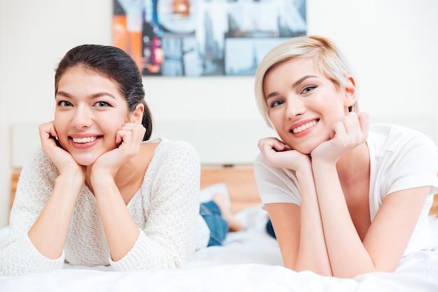 Две улыбающиеся женщины лежат на кровати и смотрят вперед