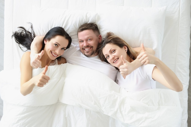 Two smiling women and man lie on bed and hold their thumbs up
