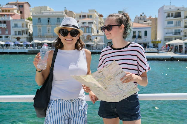Two smiling women mother and teenager daughter with map on shore of sea bay Premium Photo