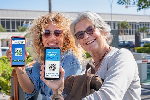 コロナウイルスのワクチン接種を受けた人々のためのデジタル健康認証を示す旅行の準備ができている2人の笑顔の女性。のんきな幸せな母と娘 Premium写真