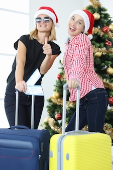 Two smiling women in santa claus hats hold suitcase and plane tickets against background of