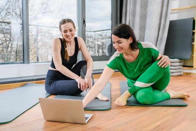 Две улыбающиеся женщины сидят на циновках с открытым экраном ноутбука и готовятся к тренировкам с онлайн-уроками