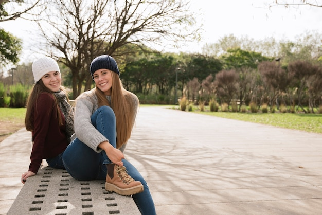 Two smiling women sitting on a bench