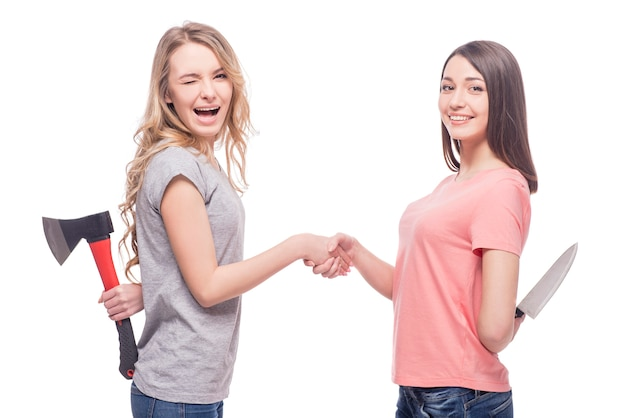 Two smiling women standing face to face and holding knife.