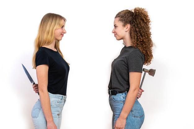 2人の笑顔の女性が向かい合って立って、後ろにナイフと斧を隠し、白い背景で隔離、隠された憎しみと偽善の概念