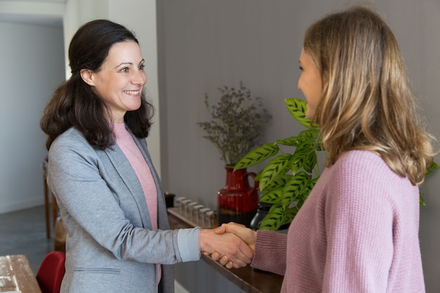Two smiling women standing and shaking hands