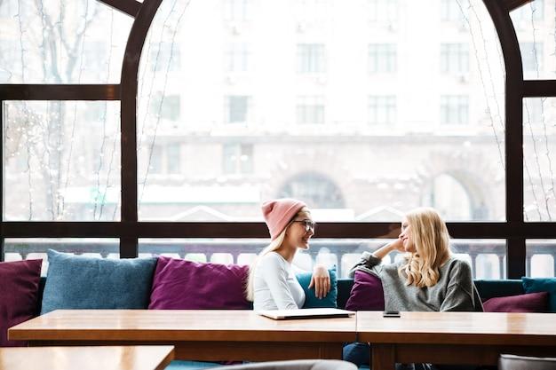 Две улыбающиеся женщины разговаривают за столом в кафе