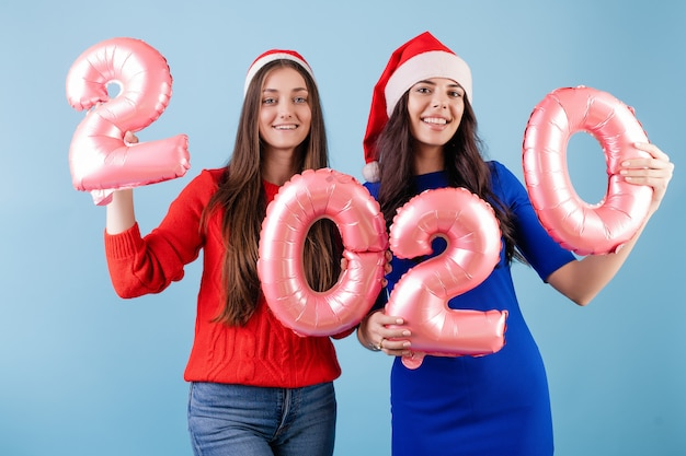 Two smiling women wearing santa hats holding 2020 balloons for new year holiday isolated over blue