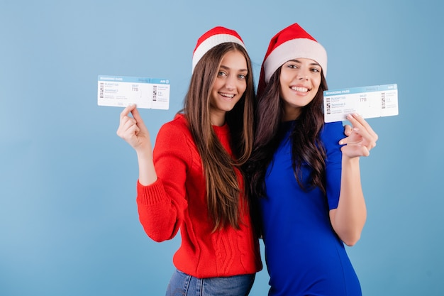 Two smiling women wearing santa hats with plane tickets isolated over blue