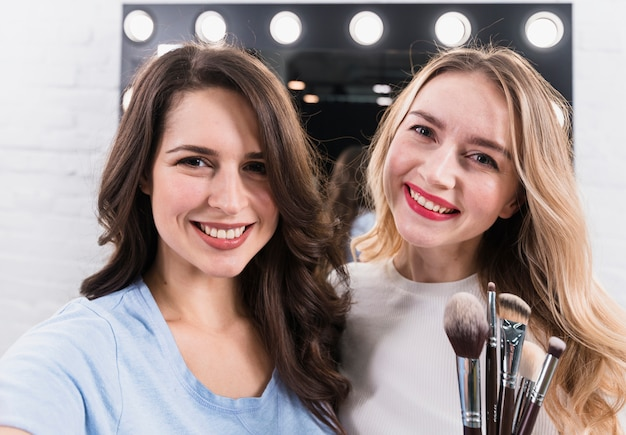 Two smiling women with brushes taking selfie at makeup mirror