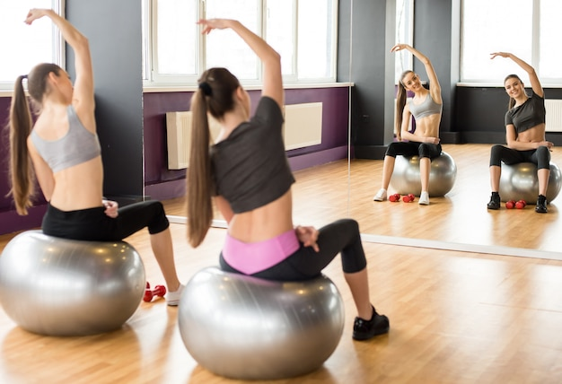 Two smiling women with exercise balls in gym.