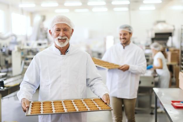 Двое улыбающихся рабочих в стерильной форме несут запеканки с печеньем. интерьер пищевой фабрики.