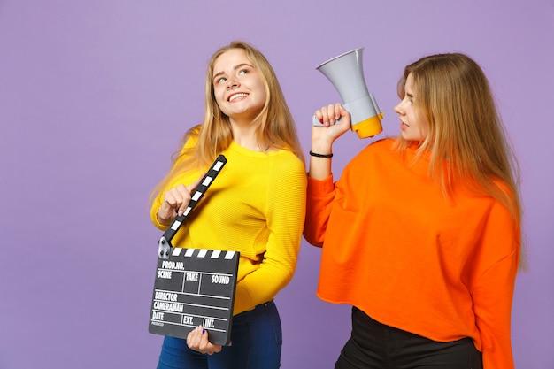 Две улыбающиеся молодые блондинки сестры-близнецы, держащие классический черный фильм, заставляют кричать с хлопушкой на мегафоне, изолированном на фиолетовой синей стене. концепция семейного образа жизни людей.