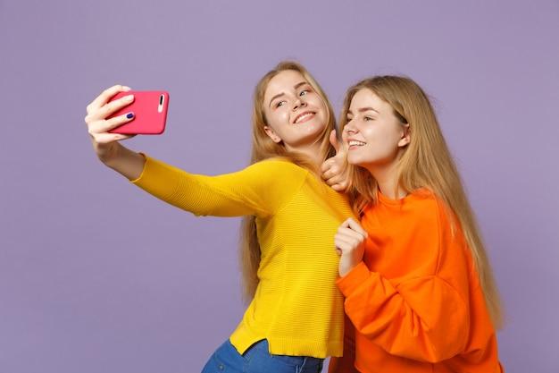 パステルバイオレットブルーの壁に分離された携帯電話でselfieショットをしているカラフルな服を着た2人の笑顔の若いブロンドの双子の姉妹の女の子。人々の家族のライフスタイルの概念。