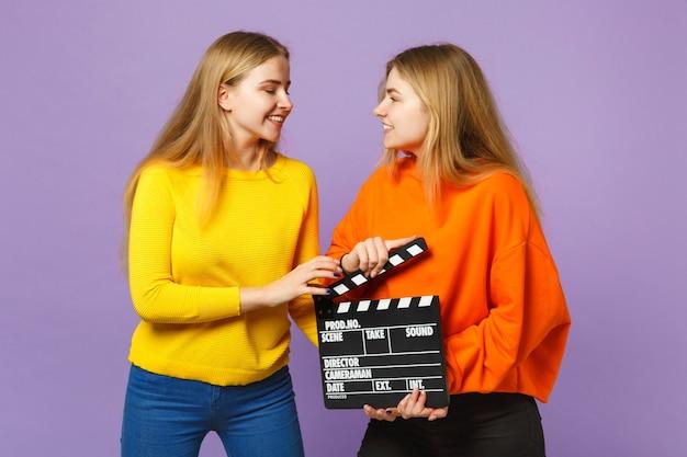 보라색 파란색 벽에 고립 된 clapperboard 만들기 클래식 블랙 영화를 들고 화려한 옷을 입고 두 웃는 젊은 금발 쌍둥이 자매 여자. 사람들이 가족 라이프 스타일 개념. .