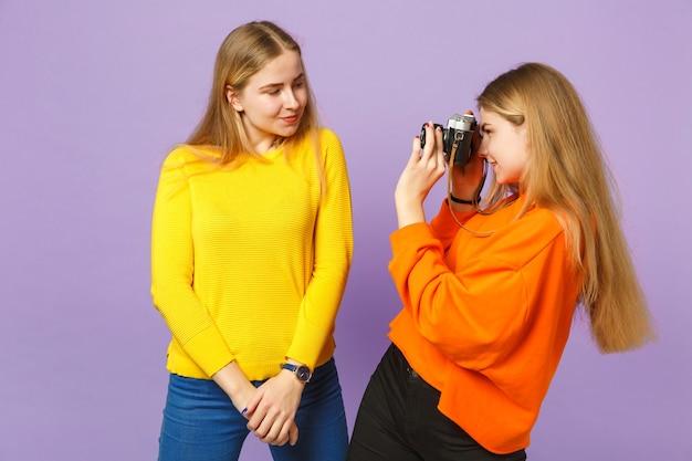 Две улыбающиеся молодые белокурые девушки сестры-близнецы в красочной одежде фотографируют на ретро-винтажную фотокамеру, изолированную на фиолетово-синей стене. концепция семейного образа жизни людей.