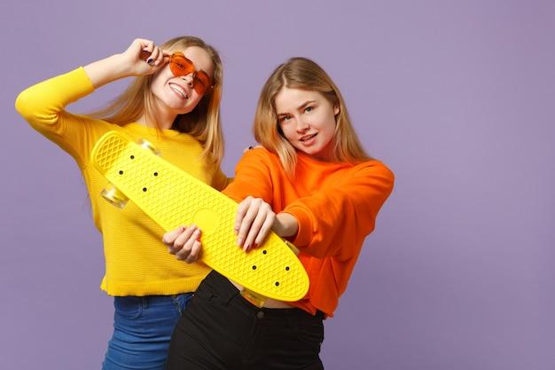 鮮やかな服を着た2人の笑顔の若い金髪の双子の姉妹の女の子、ハートの眼鏡はパステルバイオレットブルーの壁に分離された黄色のスケートボードを保持します。人々の家族のライフスタイルの概念。