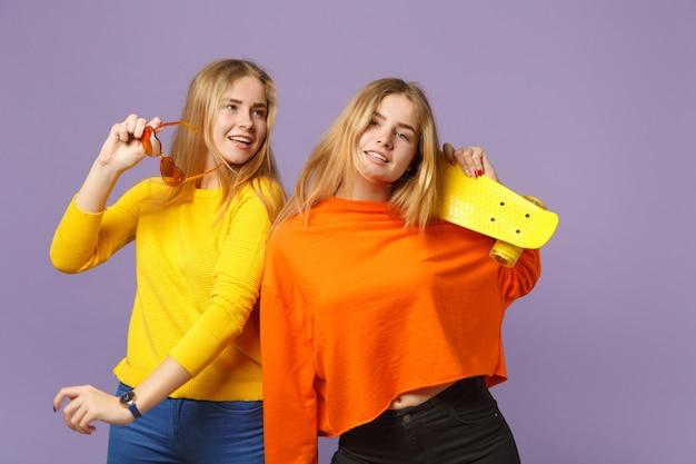 パステルバイオレットブルーの壁に分離された黄色のスケートボードを保持している鮮やかな服のハートの眼鏡の2つの笑顔の若いブロンドの双子の姉妹の女の子。人々の家族のライフスタイルの概念。