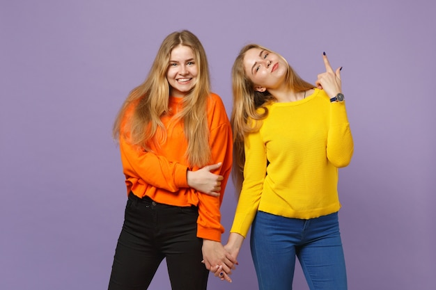 パステルバイオレットブルーの壁に人差し指を上に向けて鮮やかな服を着た2人の笑顔の若いブロンドの双子の姉妹の女の子。人々の家族のライフスタイルの概念。 。