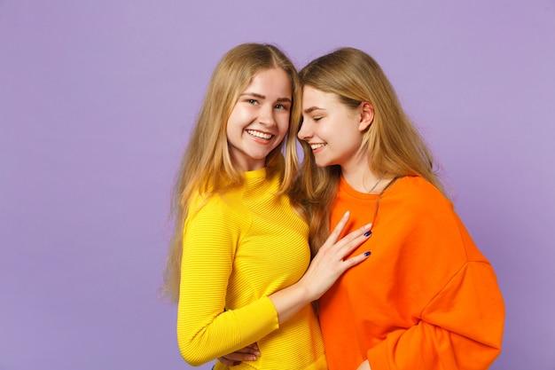 두 웃는 젊은 금발 쌍둥이 자매 여자 옆으로 파스텔 바이올렛 파란색 벽에 절연 포옹 생생한 화려한 옷을 입고. 사람들이 가족 라이프 스타일 개념.