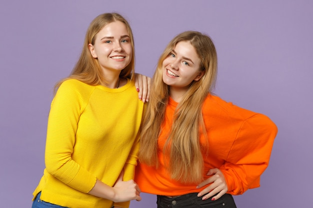 두 웃는 젊은 금발 쌍둥이 자매 소녀 서, 파스텔 바이올렛 파란색 벽에 고립 된 생생한 화려한 옷을 입고. 사람들이 가족 라이프 스타일 개념.