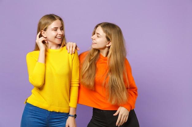 두 웃는 젊은 금발 쌍둥이 자매 여자 서, 파스텔 바이올렛 파란색 벽에 고립 된 서로보고 생생한 화려한 옷을 입고. 사람들이 가족 라이프 스타일 개념.